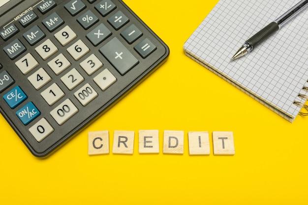 Credito di parola realizzato con lettere di legno su calcolatrice gialla e moderna con penna e taccuino.