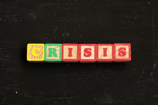 La parola crisi composta da lettere di legno giace su un tavolo nero