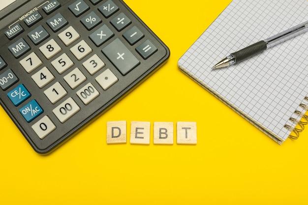 Debito di parola fatto con lettere di legno sulla calcolatrice gialla e moderna con penna e taccuino.
