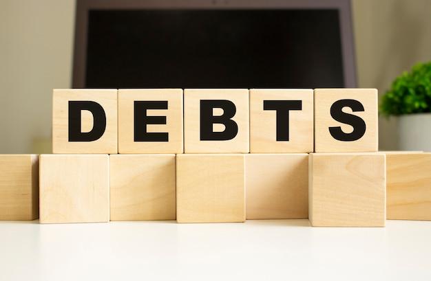 La parola debiti è scritta su cubi di legno che giacciono sul tavolo dell'ufficio davanti a un laptop.