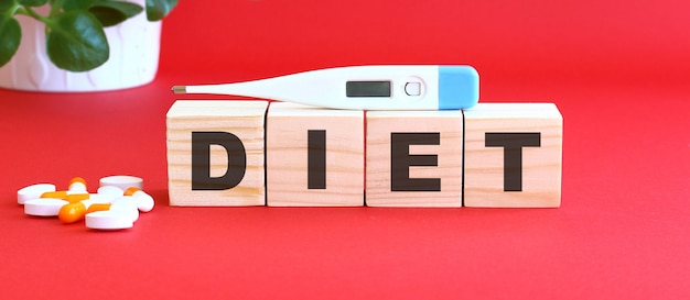 La parola dieta è composta da cubi di legno su fondo rosso con farmaci.