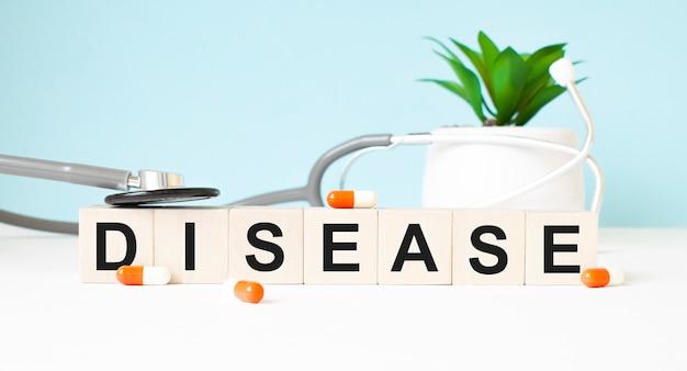 La parola malattia è scritta su cubi di legno vicino a uno stetoscopio su uno sfondo di legno. concetto medico