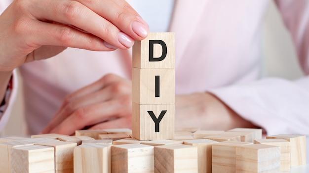 La parola fai da te su un giocattolo di legno blocca con le mani della donna, sfondo rosa.