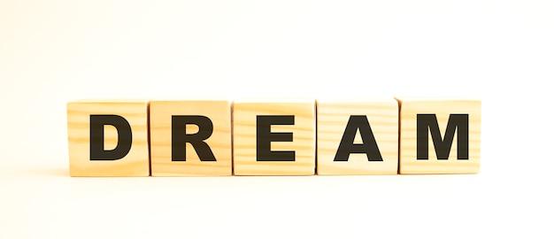 La parola dream. cubi di legno con lettere isolate su superficie bianca