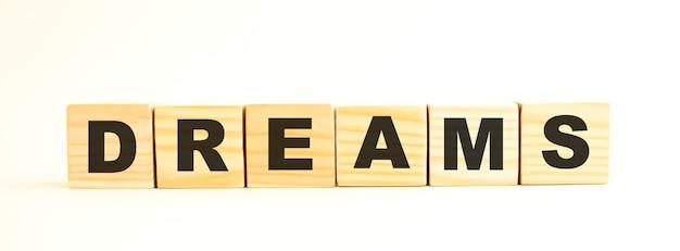 La parola sogni. cubi di legno con lettere isolate su superficie bianca