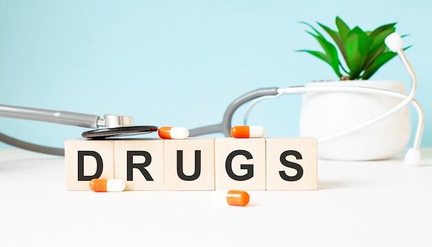 La parola droghe è scritta su cubi di legno vicino a uno stetoscopio su uno sfondo di legno. concetto medico