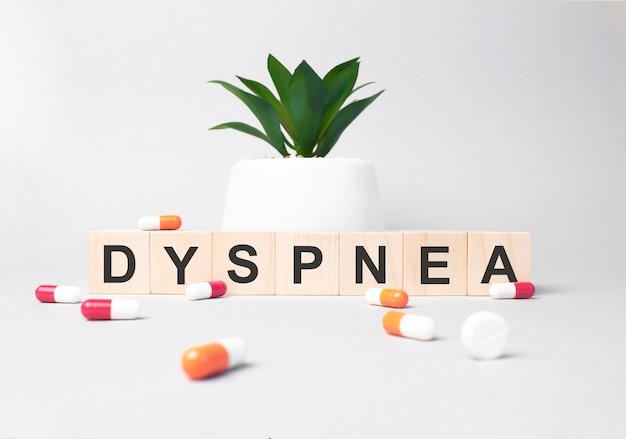Parola dyspnea composta da lettere in legno su sfondo grigio. pianta sullo sfondo. concetto medico