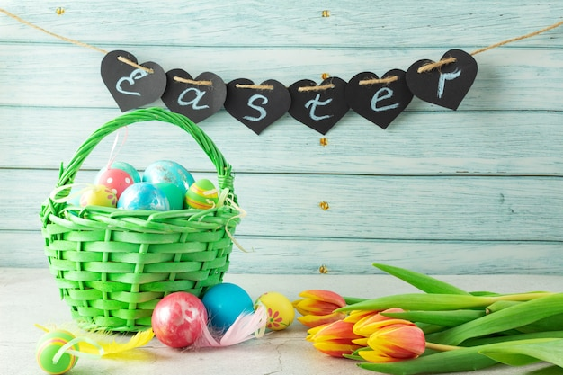 La parola pasqua su una parete in legno, uova di pasqua in un cesto e fiori tulipani
