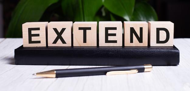 La parola estendi è scritta sui cubi di legno dell'agenda vicino al manico.
