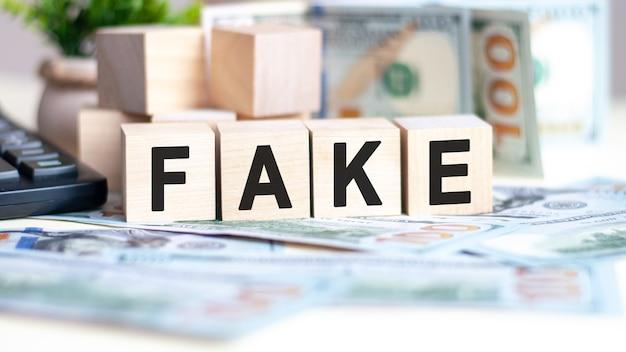 La parola falso su cubi di legno, banconote e calcolatrice sullo sfondo, affari e concetto di finanza