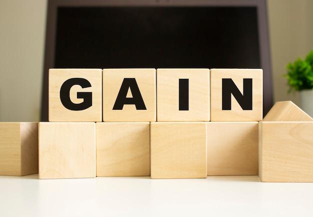 La parola gain è scritta su cubi di legno che giacciono sul tavolo dell'ufficio davanti a un laptop.
