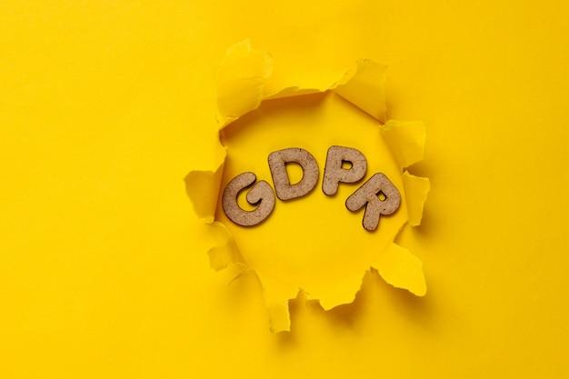 La parola gdpr in un buco strappato di superficie gialla.