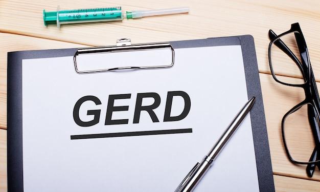 La parola gerd è scritta su un pezzo di carta bianca accanto a occhiali cerchiati di nero, una penna e una siringa. concetto medico