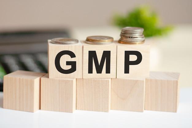 La parola gmp su cubi di legno, banconote e calcolatrice sullo sfondo. gmp - abbreviazione di good manufacturing practice