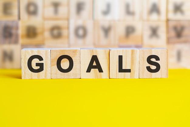 La parola goals è scritta su cubi di legno su una superficie gialla brillante. sullo sfondo ci sono file di cubi con lettere diverse. concetto di affari e finanza