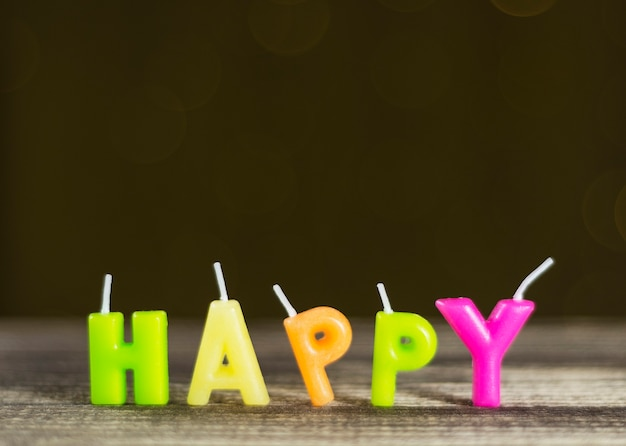 Parola felice assemblata da candele di cera di diversi colori