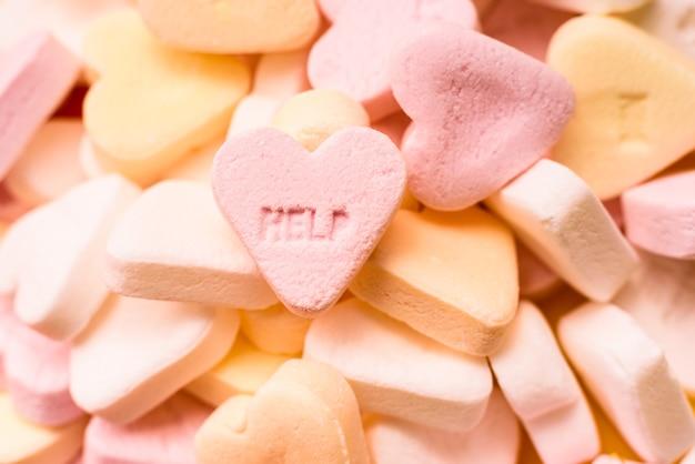 Word help inciso in una dolce caramella a forma di cuore, concetto di terapia di coppia.