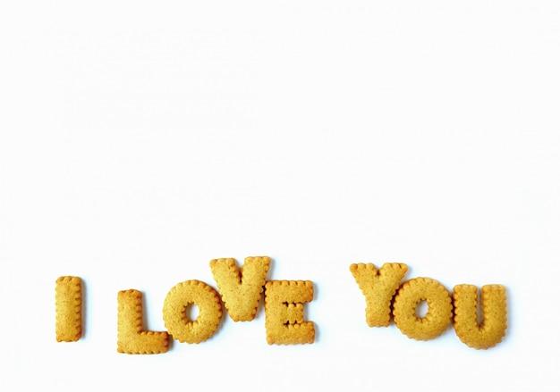 La parola ti amo scritto con biscotti a forma di alfabeto su sfondo bianco con spazio libero