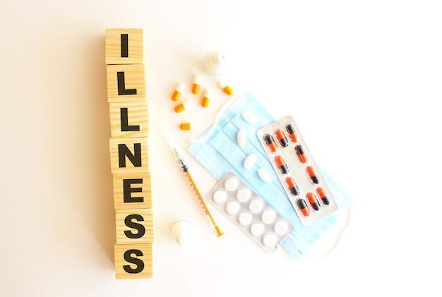 La parola malattia è composta da cubi di legno su uno sfondo bianco con farmaci e mascherina medica.
