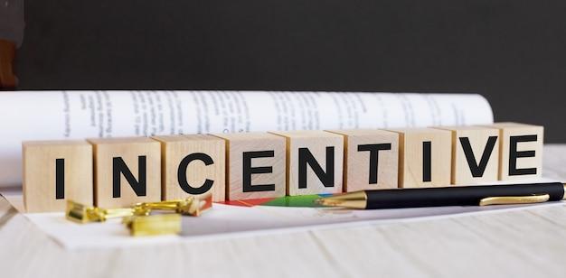La parola incentivo è scritta su cubi di legno vicino alla penna e al documento.