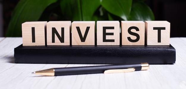La parola invest è scritta sui cubi di legno dell'agenda vicino al manico.