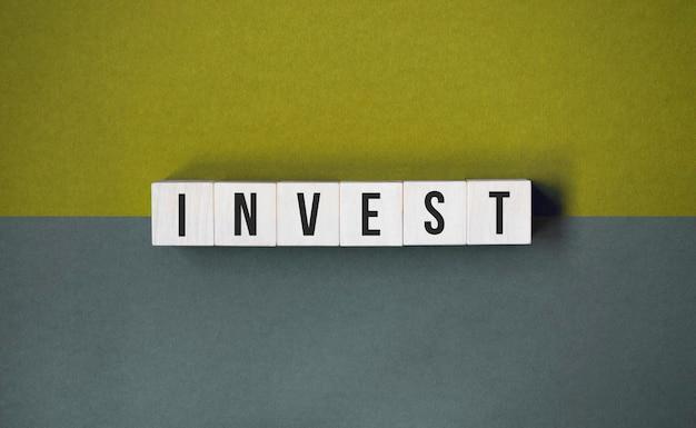 La parola investire su cubi di legno su uno sfondo grigio e giallo. concetto finanziario aziendale