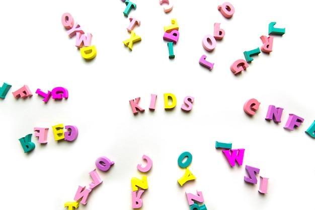 La parola bambini è composta da lettere multicolori in legno su sfondo blu per bambini