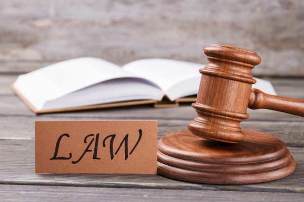 Legge di parola e martelletto di legno. libro di legge aperto sullo sfondo.