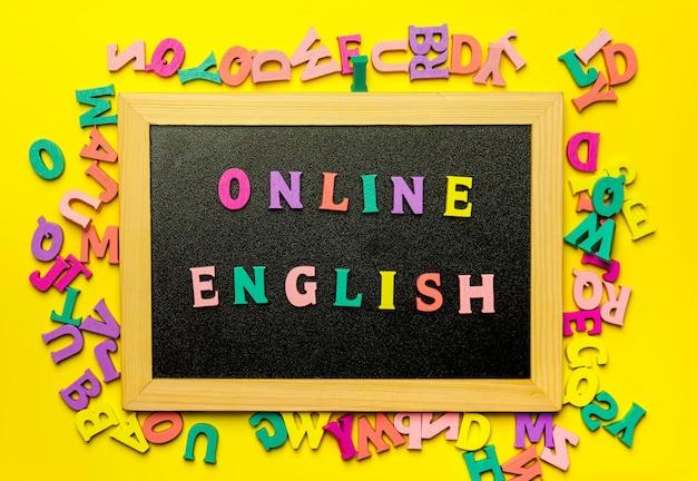Esprima l'apprendimento dell'inglese fatto con le lettere di legno sopra il bordo di legno