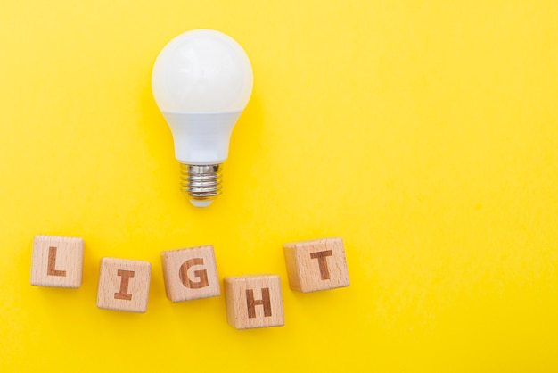 Parola luce e lampadina su sfondo giallo, immagine concettuale, layout con spazio per il testo, vista dall'alto