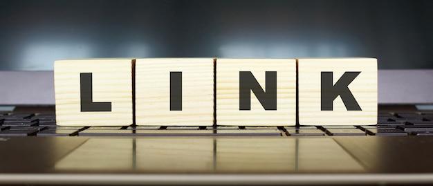 Word link cubi di legno con lettere isolate su un'immagine di concetto di affari della tastiera del computer portatile