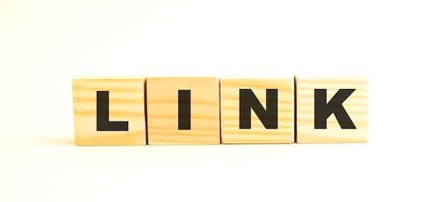 La parola link. cubi di legno con lettere isolate su superficie bianca