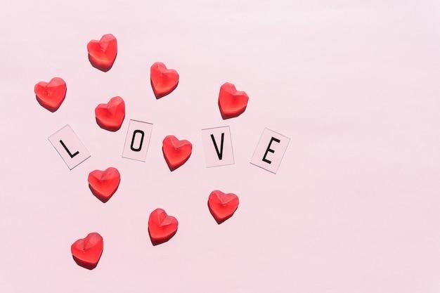 La parola amore. lettere nere amore con cuori rossi.