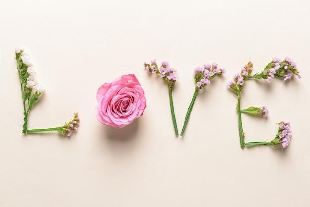 Parola amore fatta di bellissimi fiori su sfondo chiaro