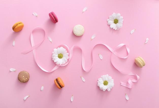 Parola amore fatta di nastro rosa con amaretti, fiori bianchi e petali