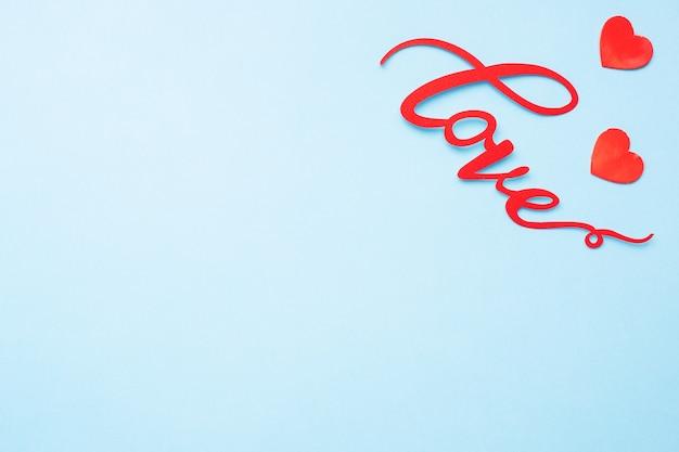 La parola amore e cuori rossi su sfondo blu, vista dall'alto. biglietto di auguri per il giorno di san valentino. lay piatto.