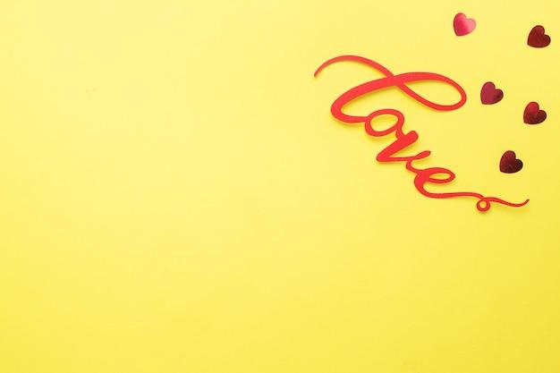 La parola amore e cuori rossi su sfondo giallo, vista dall'alto. biglietto di auguri per il giorno di san valentino. lay piatto.