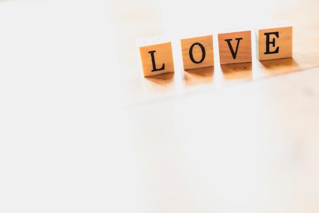 Esprima l'amore sui dadi di legno e sul fondo bianco.