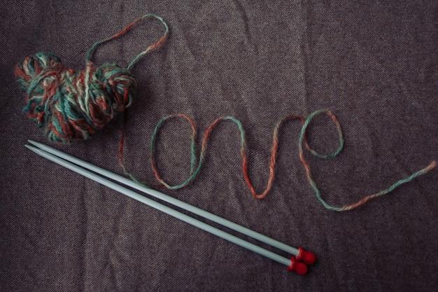 La parola amore scritta con filato di lana su fondo marrone