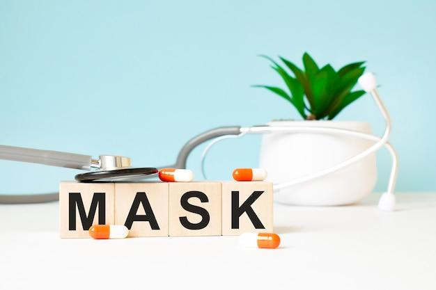 La parola maschera è scritta su cubi di legno vicino a uno stetoscopio su uno sfondo di legno. concetto medico
