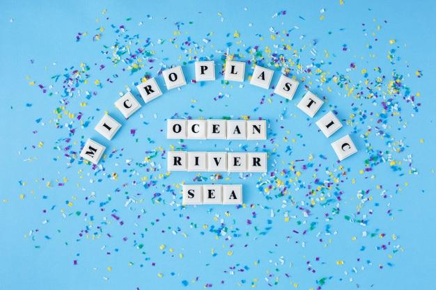 Parola microplastic ocean river sea intorno a piccole particelle di plastica su sfondo blu.