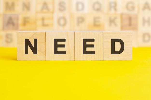 La parola bisogno è scritta su cubi di legno su una superficie gialla brillante. sullo sfondo ci sono file di cubi con lettere diverse. concetto di affari e finanza