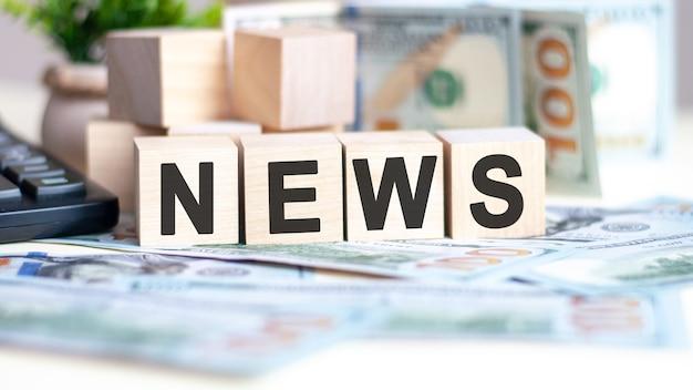 La parola news su cubi di legno, banconote e calcolatrice sulla superficie