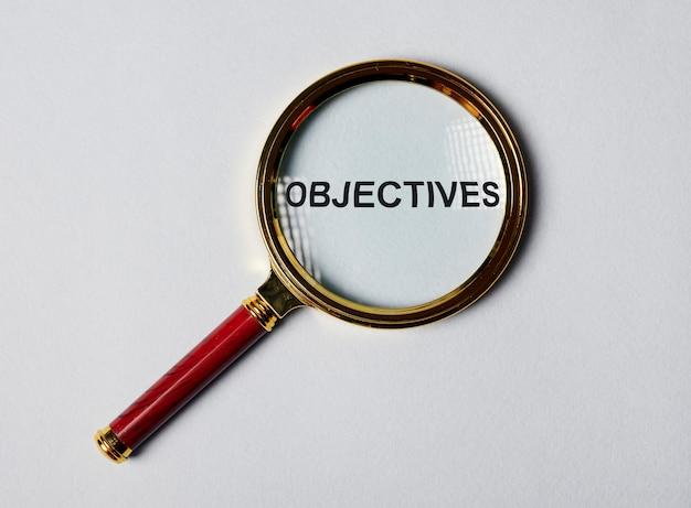 Obiettivi di parola attraverso la lente di ingrandimento sul concetto di obiettivo di sfondo blu gary