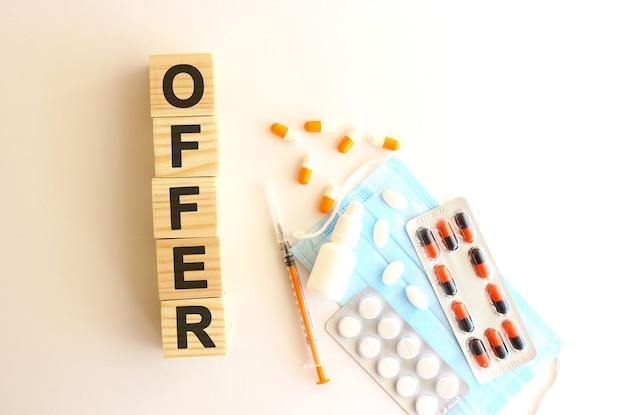 La parola offerta è composta da cubi di legno su fondo bianco con farmaci e mascherina medica.