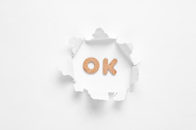 Parola ok nel foro strappato isolato su bianco