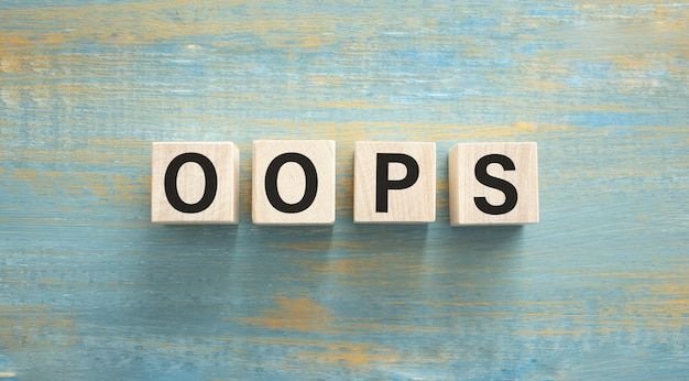 Parola oops. cubi di legno con lettere isolate su sfondo blu con copia spazio disponibile. immagine di concetto.