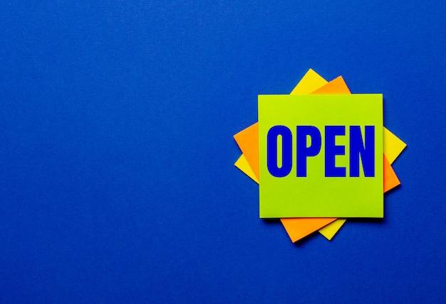 La parola aperto è scritta su adesivi luminosi su sfondo blu