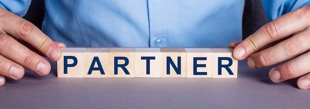 La parola partner è composta da cubi di legno da un uomo
