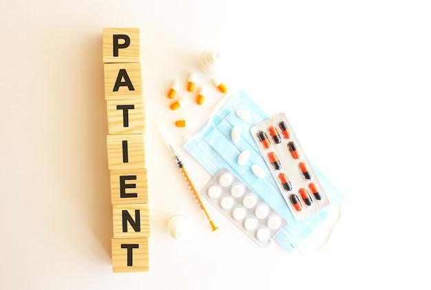 La parola paziente è composta da cubi di legno su uno sfondo bianco. concetto medico.